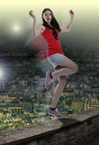 Woman in danger balancing on one leg at the edge over city Royalty Free Stock Photo