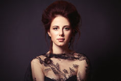 Woman on dark background. Portrait of a beautiful woman in style dress on dark backgorund royalty free stock image