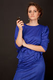 Woman in dark blue dress with cellphone looking to the camera Royalty Free Stock Images