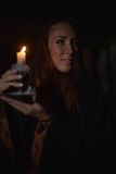 Woman in the dark with a candle Stock Images