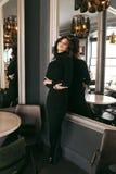 Woman with dark curly hair in elegant dress sitting in elegant r Stock Photos