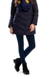 Woman in dark down jacket. Navy pants and black boots. Fashionable winter clothing. Warm footwear from boutique Stock Photo