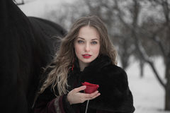 Woman in a dark dress with a red rose in winter Royalty Free Stock Image