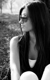 Woman in dark glasses. Beautiful young woman in dark glasses in park. black-and-white image Stock Photography