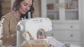 Woman with dark hair in a beige dress is engaged in sewing stock video
