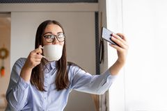A woman with dark hair, in a blue shirt with a Cup of coffee in her hands in a cafe takes a selfie stock photos