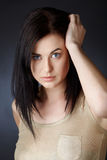 Woman with dark hair in bob. Beautiful young woman with blue eyes and dark hair in structured bob haircut touching her hair with curious expression Royalty Free Stock Photos