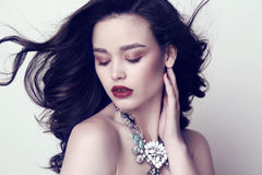 Woman with dark hair and bright makeup with luxurious bijou. Fashion studio photo of beautiful sensual woman with dark hair and bright makeup with luxurious Royalty Free Stock Images
