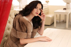 Woman with dark hair in elegant clothes and luxurious fur coat. Fashion outdoor photo of gorgeous sensual woman with dark hair in elegant clothes and luxurious stock images