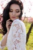 Woman with dark hair  in elegant dress posing in blossom garden Stock Photo