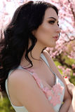 Woman with dark hair  in elegant dress posing in blossom garden Royalty Free Stock Photos