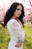 Woman with dark hair  in elegant dress posing in blossom garden Royalty Free Stock Photo