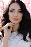 Woman with dark hair  in elegant dress posing in blossom garden Royalty Free Stock Images