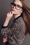 Woman with dark hair in elegant leopard print shirt and with glasses Stock Images