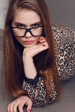 Woman with dark hair in elegant leopard print shirt and with glasses Royalty Free Stock Image