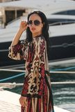 Woman with dark hair in elegant swimming suit posing near yachts in pier Stock Photography
