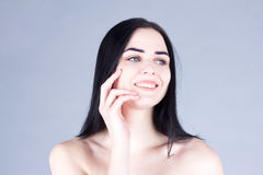 Woman with dark hair laughing and touching her cheek by hand. Beauty concept Royalty Free Stock Image