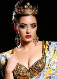 Woman with dark hair in luxurious gold dress with bijou and crown, stock image