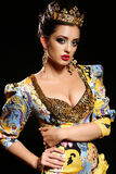Woman with dark hair in luxurious gold dress with bijou and crown, royalty free stock images