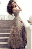 Woman with dark hair in luxurious sequin dress posing on stairs Stock Images