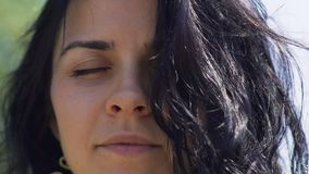 Woman with dark hair meditates with closed eyes outdoors, inner temple oneness. Stock footage stock video