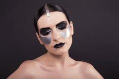 Woman with dark  hair and metallic extraordinary makeup Royalty Free Stock Photos