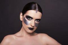 Woman with dark  hair and metallic extraordinary makeup Stock Photos