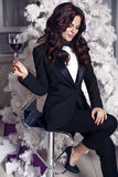Woman with dark hair wearing elegant black suit,holding a glass of wine. Fashion interior photo of beautiful woman with dark hair wearing elegant black suit Royalty Free Stock Photos