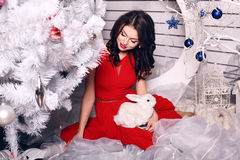Woman with dark hair wearing elegant red dress  posing beside a Christmas tree Royalty Free Stock Photography