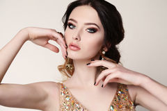 Woman with dark hair wearing luxurious sequin dress and bijou Royalty Free Stock Images