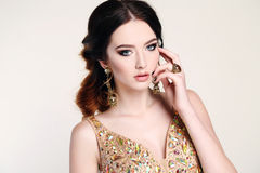 Woman with dark hair wearing luxurious sequin dress and bijou stock photography