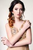 Woman with dark hair wearing luxurious sequin dress and bijou Stock Photos