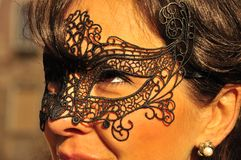 Woman with a dark mask. Close up portrait of woman with a mask on her eyes in Venice Stock Photo