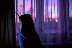 Woman in dark room on sunset window background Royalty Free Stock Image