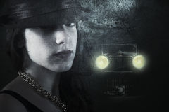 Woman in a dark street. Composite and textured 1930's style imagery with a young woman in dark street followed by a strange retro car royalty free stock photos