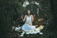 Woman in dark wood surrounded by books. And pages . Surreal and weird Stock Image