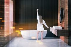 Woman in dark wooden bathroom interior, sink, tub. Woman in interior of modern bathroom with dark wooden and beige walls, concrete floor, white tub and sink stock photo