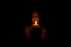 Woman in darkness with candle light Stock Photography