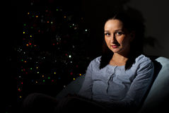 Woman in darkness by Christmas tree Stock Images