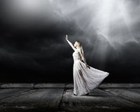 Woman in darkness. Young woman in in darkness reaching to sun light royalty free stock images
