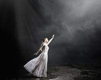 Woman in darkness. Young woman in in darkness reaching to sun light Stock Images