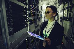 Woman in data centre. Attractive woman is working in data centre with tablet.IT engineer specialist in network server room.Running diagnostics and maintenance royalty free stock photography