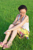 Woman daub cream in field. Beautiful Asia woman daubs cream outdoor to protect the sunshine (summer care) or mosquito bite Stock Image