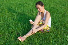 Woman daub cream in field. Beautiful Asia woman daubs cream outdoor to protect the sunshine (summer care) or mosquito bite Royalty Free Stock Photos