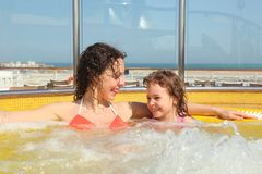 Woman with daughter both smiling in hot tub. Beautiful woman with her daughter both smiling in hot tub on cruise ship Royalty Free Stock Photo