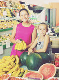 Woman with daughter buying bananas Stock Photo