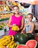 Woman with daughter buying bananas Royalty Free Stock Photos