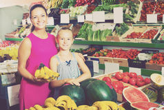 Woman with daughter buying bananas Royalty Free Stock Image