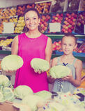 Woman with daughter buying cabbage  in marketplace Royalty Free Stock Photography