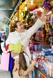 Woman with  daughter buying gifts at Christmas market Stock Photography